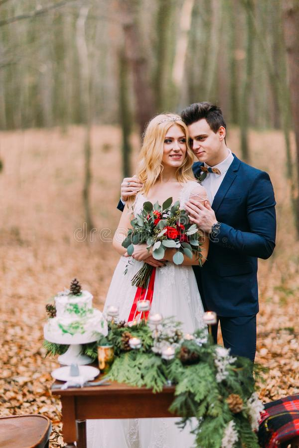 Beautiful wedding couple posing near the vintage table in autumn forest royalty free stock image