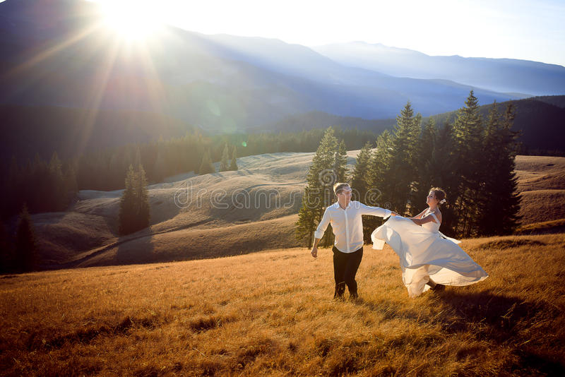 Beautiful wedding couple running and having fun on the field surrounded by mountains stock photos