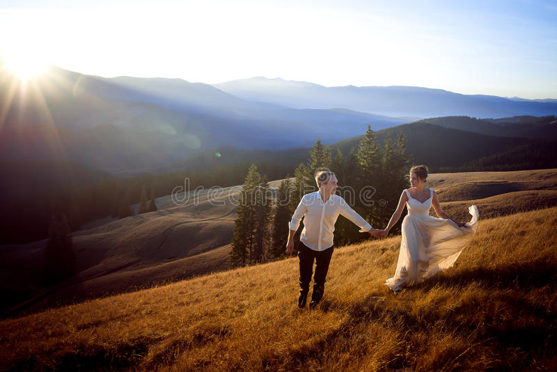 Beautiful wedding couple running and having fun on the field surrounded by mountains stock images