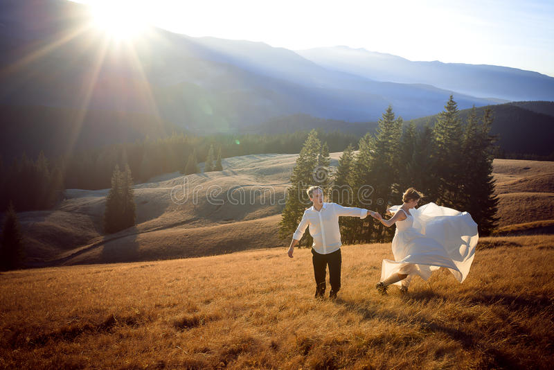 Beautiful wedding couple running and having fun on the field surrounded by mountains royalty free stock photo