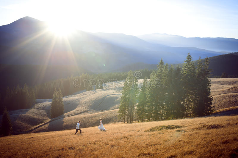 Beautiful wedding couple running and having fun on the field surrounded by mountains stock photo