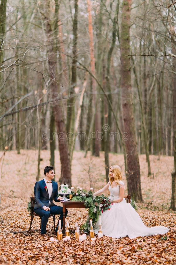 Beautiful wedding couple sitting at the vintage table in autumn forest stock photos
