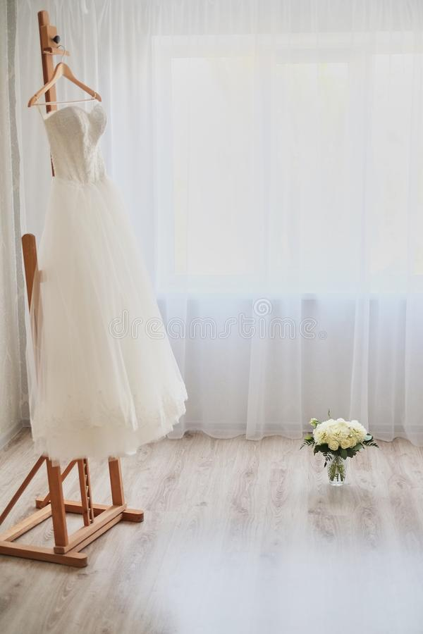 Beautiful wedding dress on hanger in room stock photos