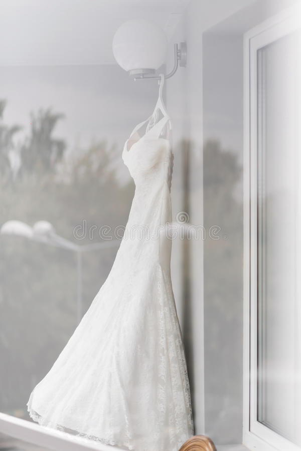 Beautiful wedding dress on hanger in room. the light from the window stock photography