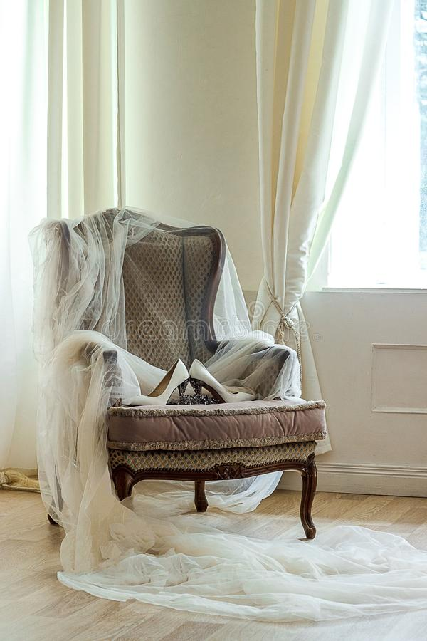 Wedding shoes on a luxurious armchair. Beautiful wedding flowers and shoes on an luxury armchair royalty free stock image