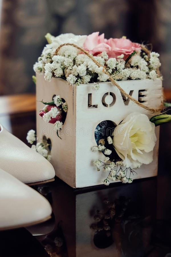 Beautiful wedding flowers in a wooden basket and white bride shoes on a dark glass table royalty free stock images