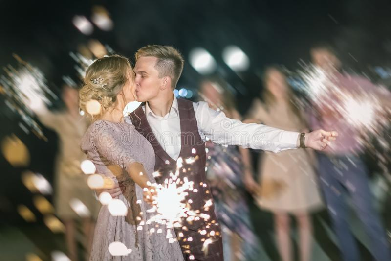 Beautiful wedding finale, the bride and groom and their guests lit sparklers in the street royalty free stock photo