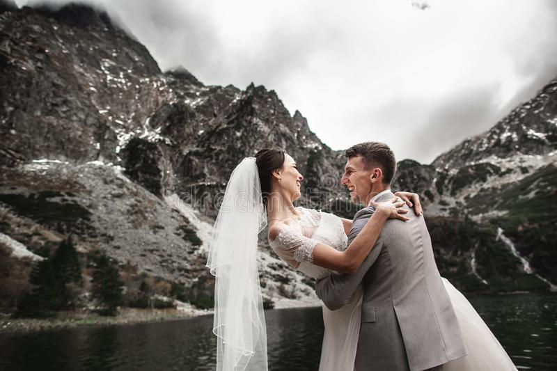 Beautiful wedding photosession. The groom circles his young bride, on the shore of the lake Morskie Oko. Poland royalty free stock photos