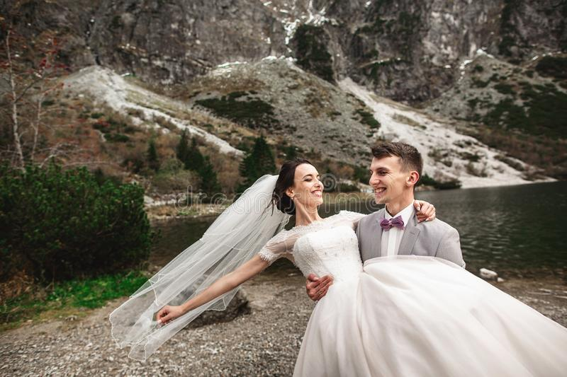 Beautiful wedding photosession. The groom circles his young bride, on the shore of the lake Morskie Oko. Poland royalty free stock image
