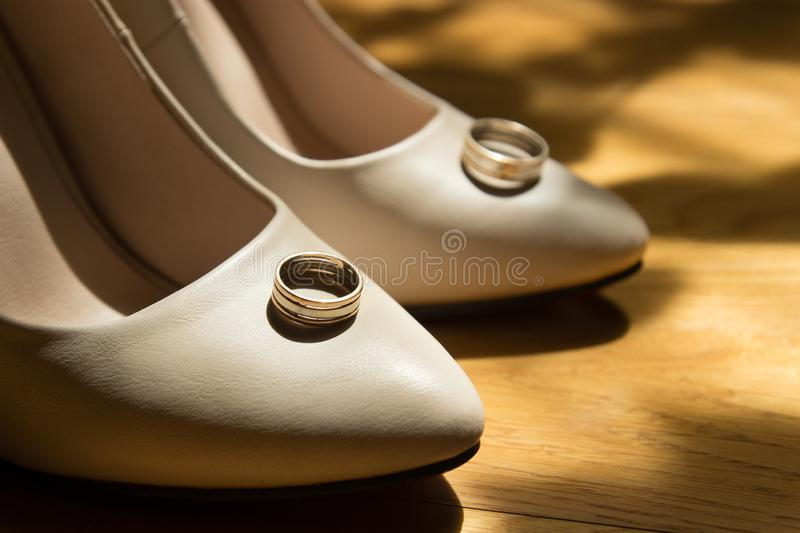 Beautiful wedding ring on the bride`s white shoes. Beautiful wedding ring on the fasion bride`s white shoes stock photo