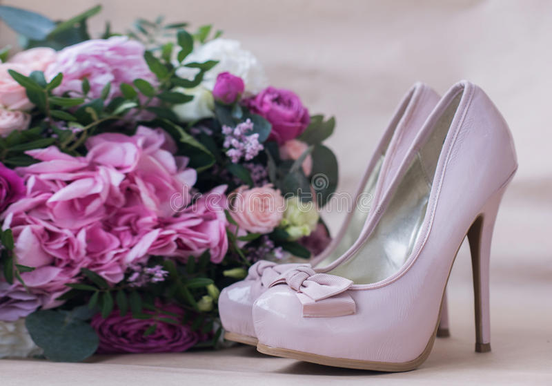 Beautiful wedding shoes with high heels and a bouquet of colorful flowers stock photography