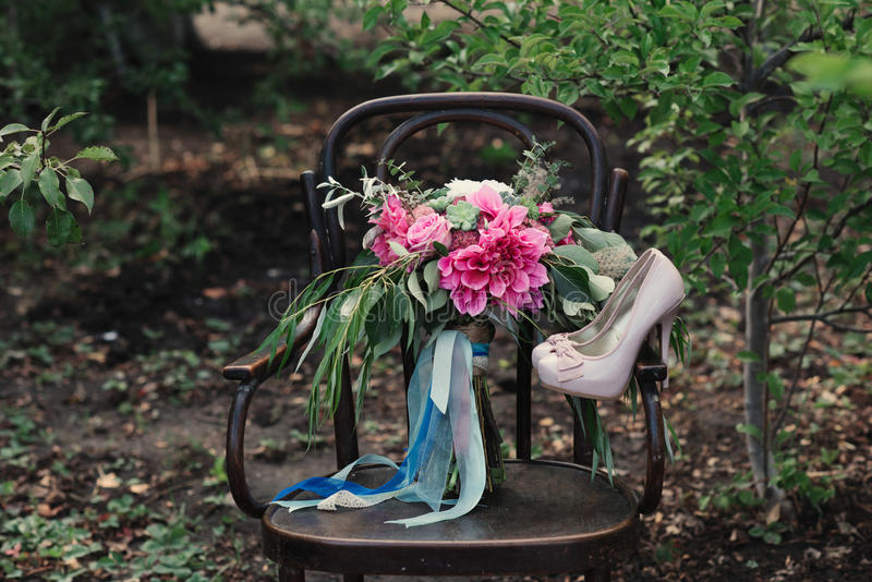 Beautiful wedding shoes with high heels and a bouquet of colorful flowers on a vintage chair on the nature royalty free stock image