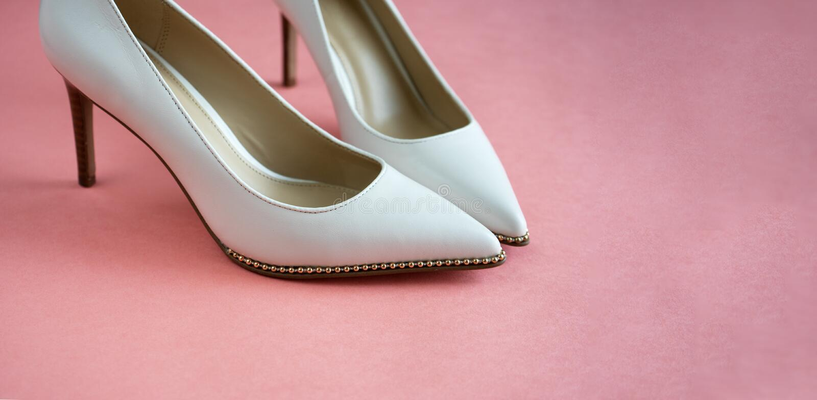 Beautiful wedding shoes on a high and thin gold stiletto. Luxurious designer wedding shoes on a pink table stock image