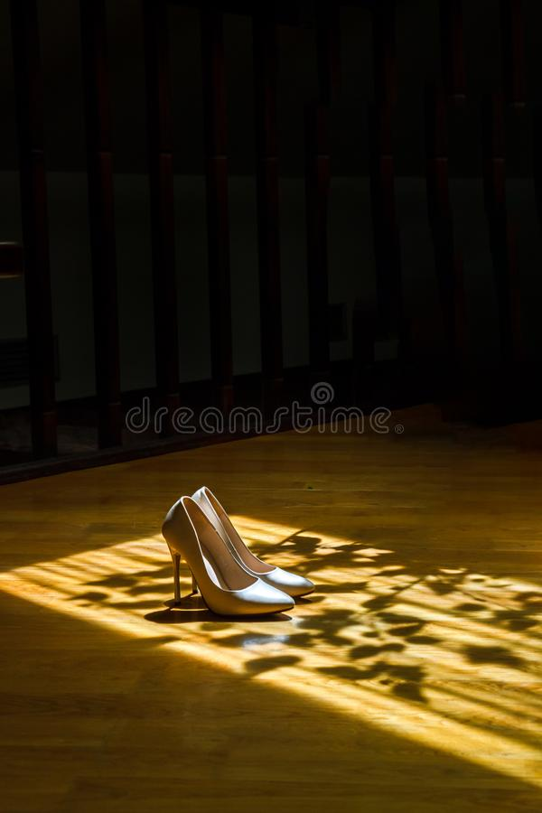 Beautiful wedding shoes in shade in sunlight. Wedding shoes, partially illuminated by sunlight, partially in the shade stock images