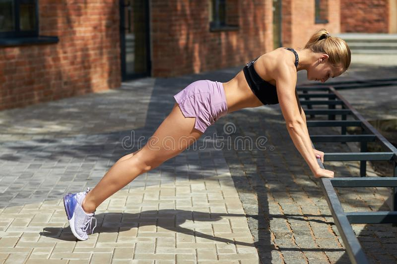 Beautiful well-built girl in black stylish top, shorts doing morning exercises. Full length side view photo. daily life, routine stock images