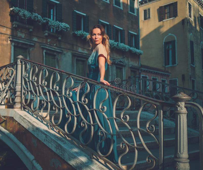 Beautiful well-dressed woman posing on a bridge over the canal in Venice. royalty free stock image