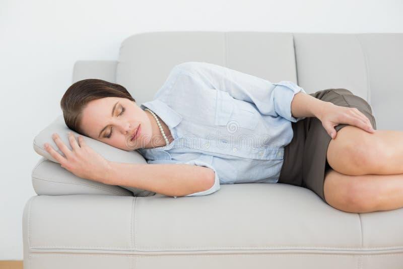 Beautiful well dressed woman sleeping on sofa stock photography