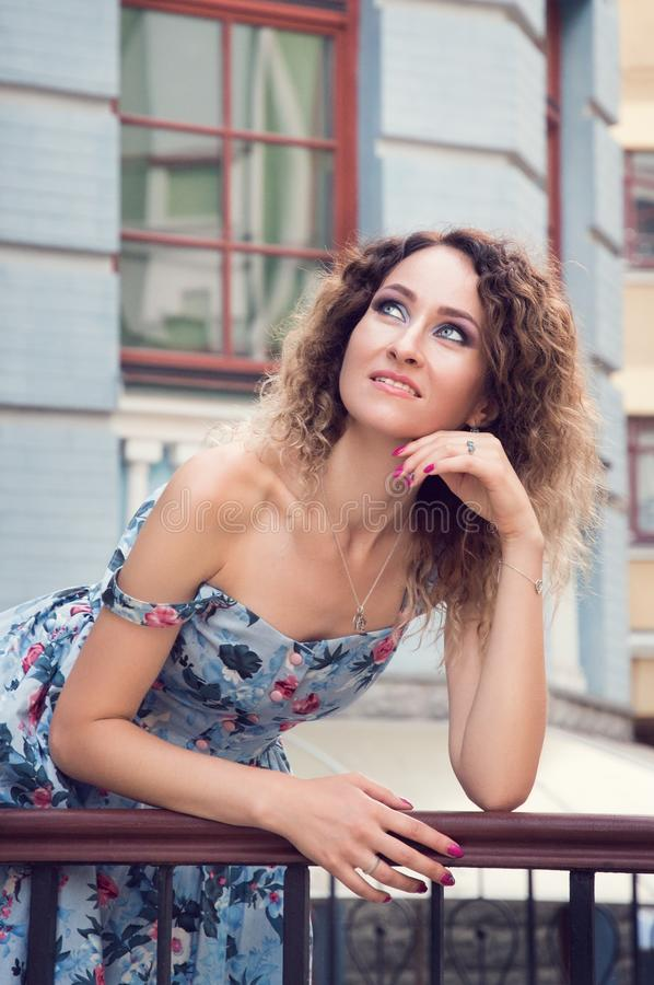 Beautiful well-groomed girl in a blue dress leaned on the railing of the old blue building. She happily smiles and dreamily looks royalty free stock photo