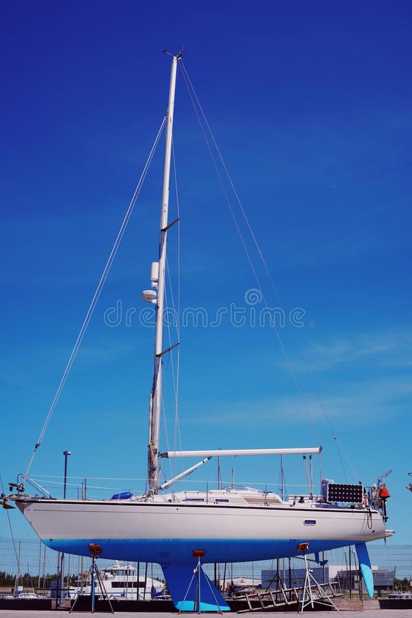 Beautiful white blue sailing boat stands on the dock and waits for the launch.summer. Beautiful white blue sailing boat stands on the dock and waits for the stock images