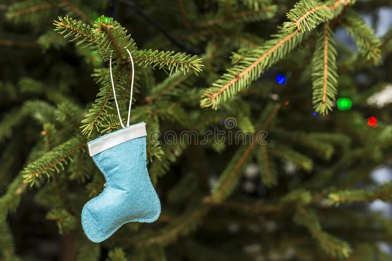Beautiful white-blue toy - a fabric boot of Santa Claus on a Christmas tree with a garland, on a blurred background. Beautiful white-blue toy - a fabric boot of royalty free stock photo