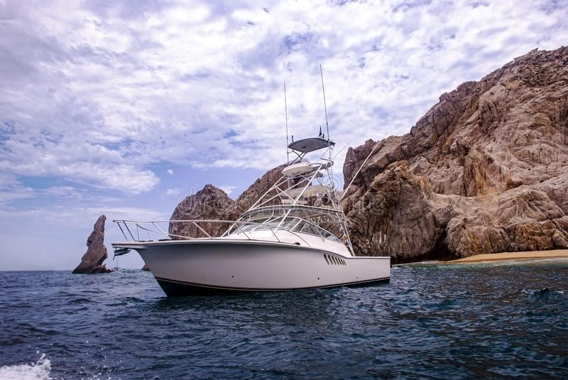 Beautiful white boat by the rocks royalty free stock images
