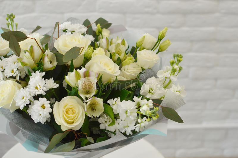 Beautiful white bouquet of flowers in stylish paper. royalty free stock image