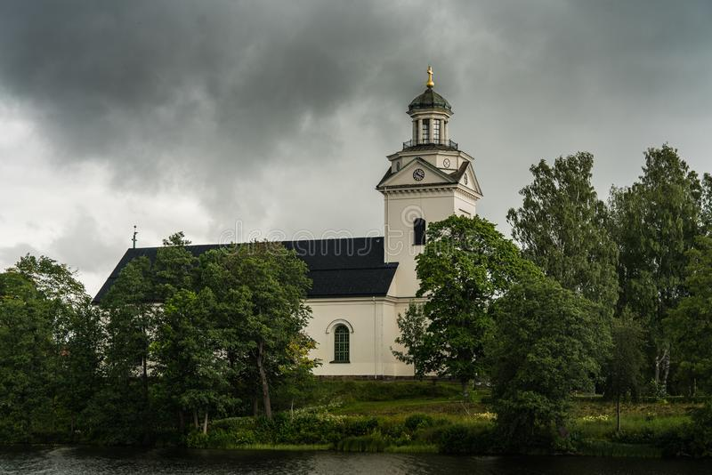 White church with overcast sky. Beautiful white church in Sweden, standing in a lush green environment with a dark overcast sky royalty free stock images