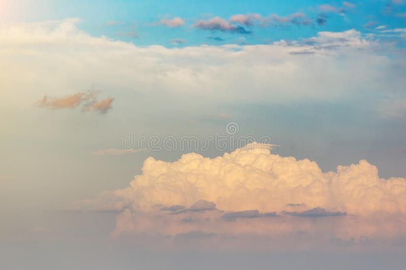 Beautiful white clouds on blue sky. Beautiful fluffy cumulus clouds in the blue sky, golden sunset sun royalty free stock image