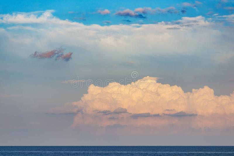 Beautiful white clouds on blue sky. Beautiful fluffy cumulus clouds in the blue sky, golden sunset sun royalty free stock photography