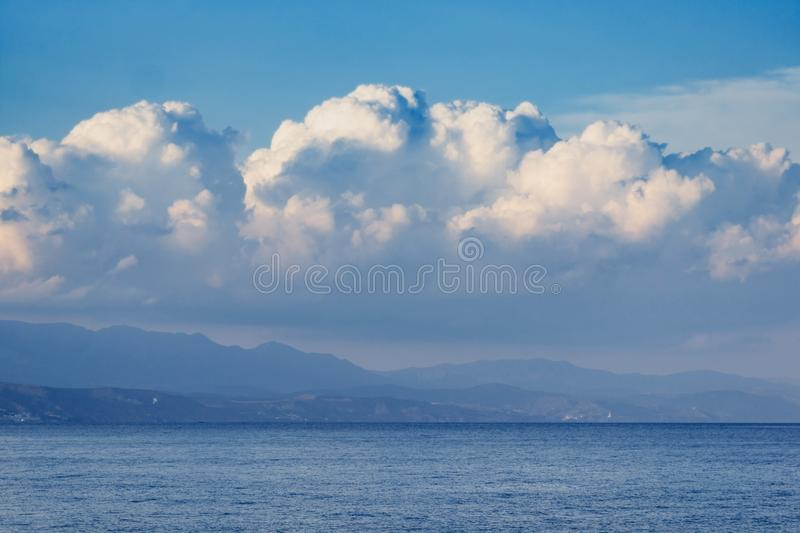 Beautiful white clouds on blue sky, and mountins. Beautiful fluffy cumulus clouds in the blue sky, golden sunset sun.Landscape with mountains and the sea stock photography