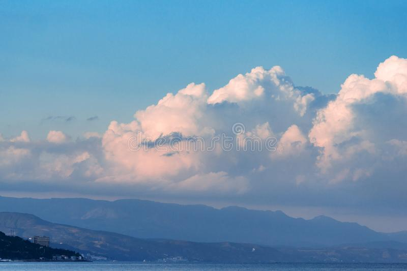Beautiful white clouds on blue sky, and mountins. Beautiful fluffy cumulus clouds in the blue sky, golden sunset sun.Landscape with mountains and the sea royalty free stock photo
