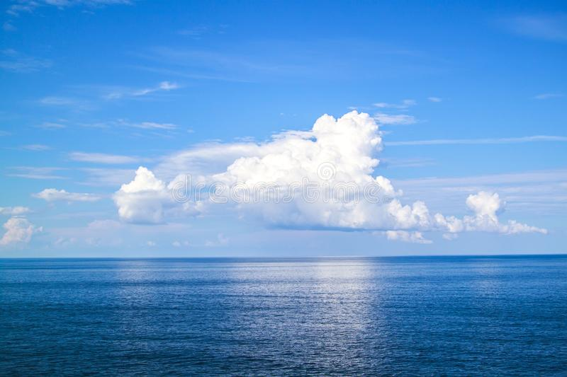 beautiful white clouds on blue sky over calm sea stock photo