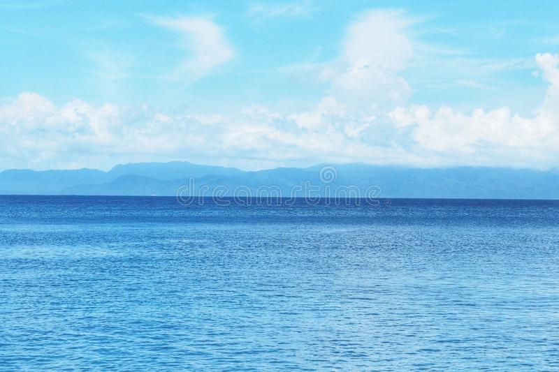 Beautiful white clouds on blue sky over calm sea with sunlight reflection, Sunny sky and calm blue ocean stock image