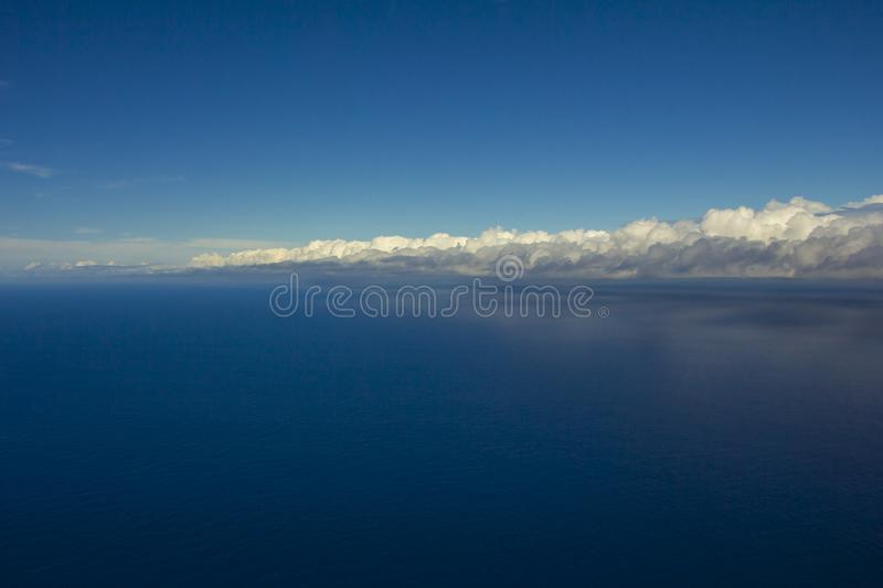 Beautiful clouds over the sea. Beautiful white clouds forming and moving in blue sky royalty free stock photography