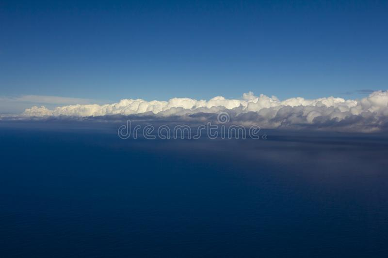 Beautiful clouds over the sea. Beautiful white clouds forming and moving in blue sky stock photos