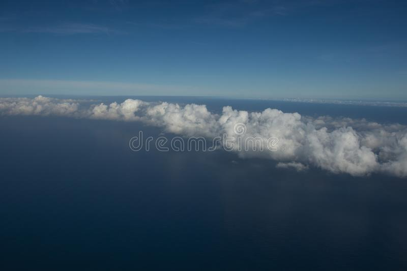 Beautiful clouds over the sea. Beautiful white clouds forming and moving in blue sky royalty free stock photo