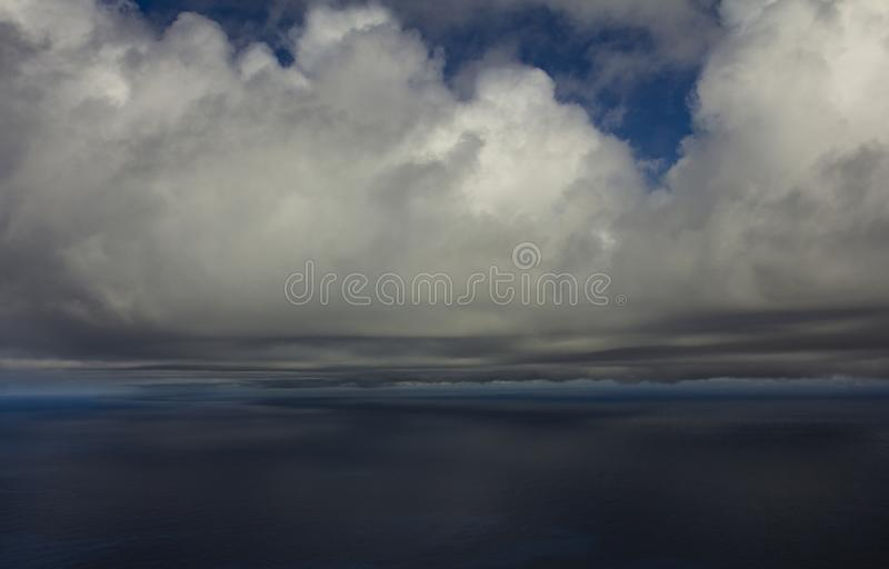 Beautiful clouds over the sea. Beautiful white clouds forming and moving in blue sky stock photography
