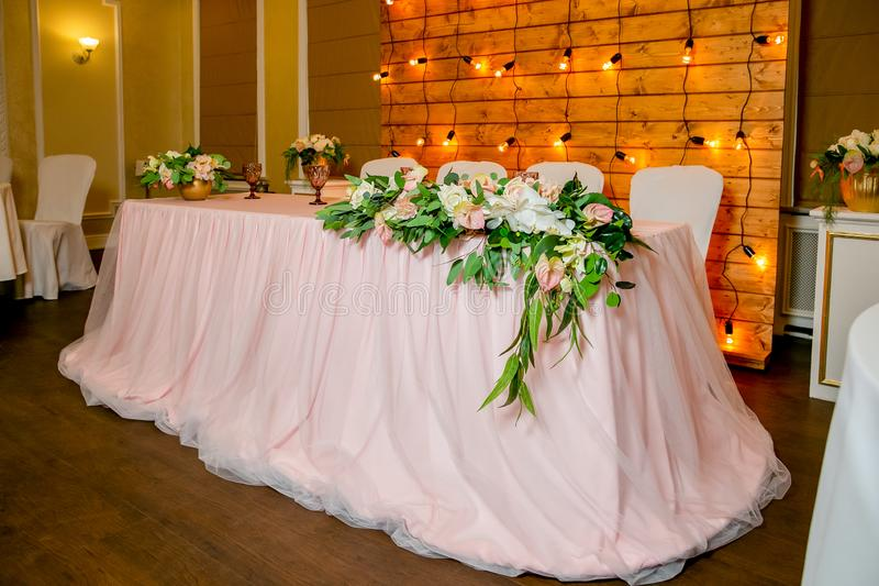 Beautiful white dinner table for newlyweds decorated with greenery and long cloth. A long flower arrangement on the table, a royalty free stock photography