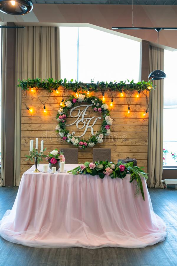 Beautiful white dinner table for newlyweds decorated with greenery and long cloth. A long flower arrangement on the table, a stock image