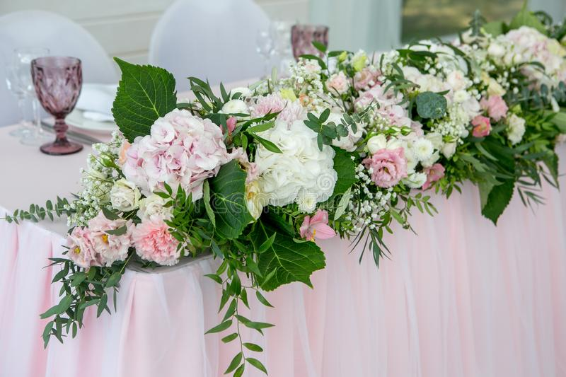 Beautiful white dinner table for newlyweds decorated with greenery and long cloth. Long flower arrangement of hydrangeas, roses, g. Ipsophiles, lilies and royalty free stock images