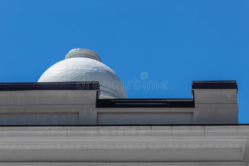 Beautiful white dome on the roof of a building with black trim, blue sky copy space. Horizontal aspect stock photo