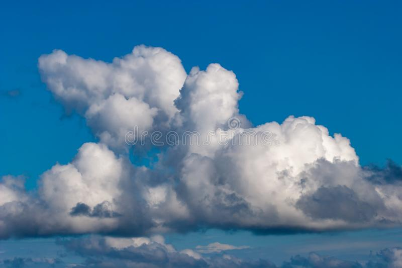 Beautiful white fancy clouds illuminated by the sun on a blue sky. royalty free stock image