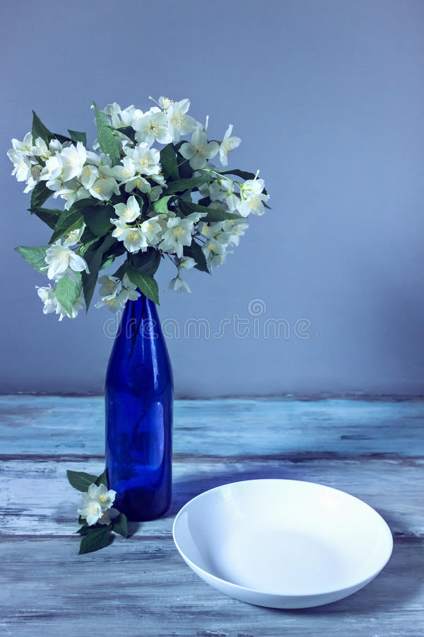 Beautiful white flowers in bottle. Beautiful white flowers in blue bottle. jasmin. wooden grey background stock image