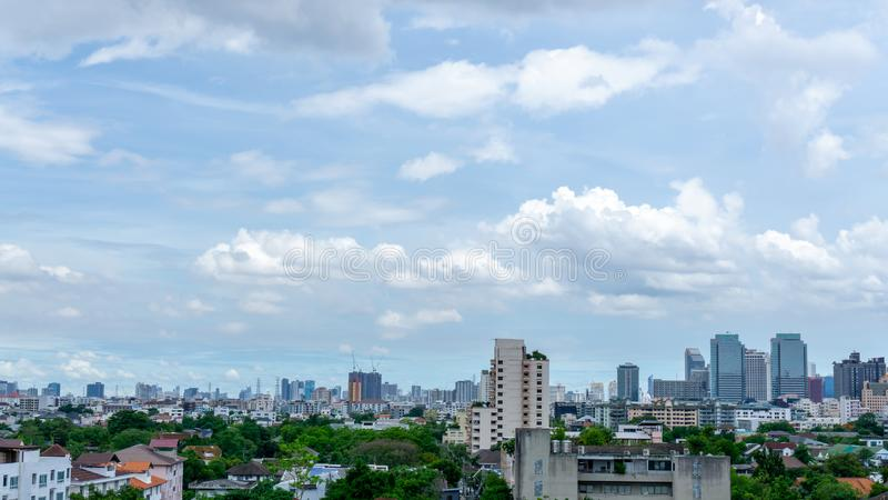 Beautiful white fluffy cloud formation on vivid blue sky in a sunny day above big city, view from rooftop. Of the building stock image