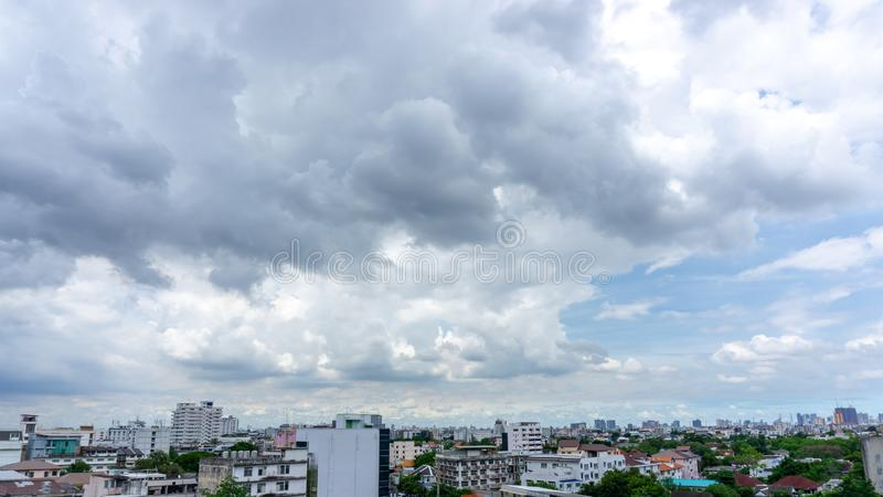 Beautiful white fluffy cloud formation on vivid blue sky in a sunny day above big city, view from rooftop. Image royalty free stock photography