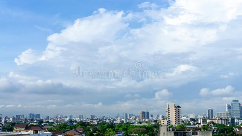 Beautiful white fluffy cloud formation on vivid blue sky in a sunny day above big city, view from rooftop a part of Bangkok. In Thailand royalty free stock photo