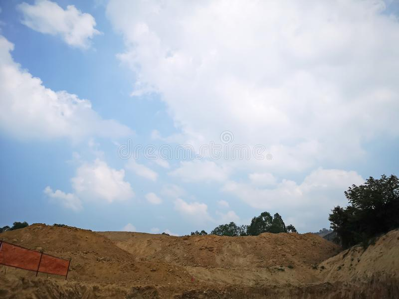 Beautiful white fluffy clouds on vivid blue sky above brown land at infrastructure on ground,  construction site area in a suny. Beautiful white fluffy clouds on royalty free stock photo
