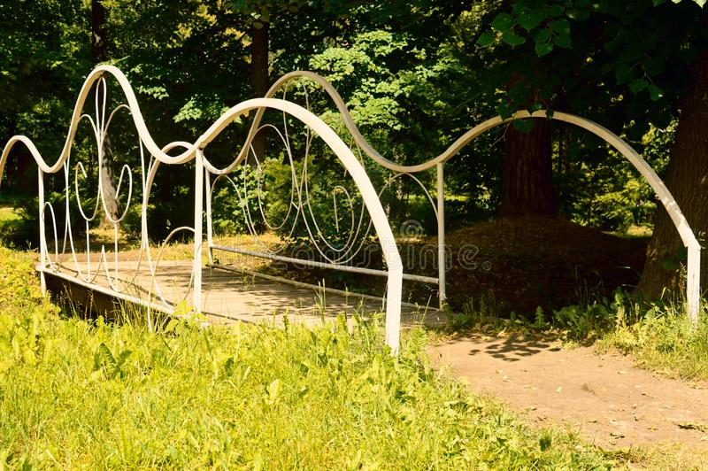 The white forged bridge in a garden royalty free stock image