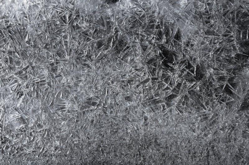 Beautiful white frozen ice crystals, crack texture on black background, winter seasonal backdrop. Frosty ice patterns stock photo