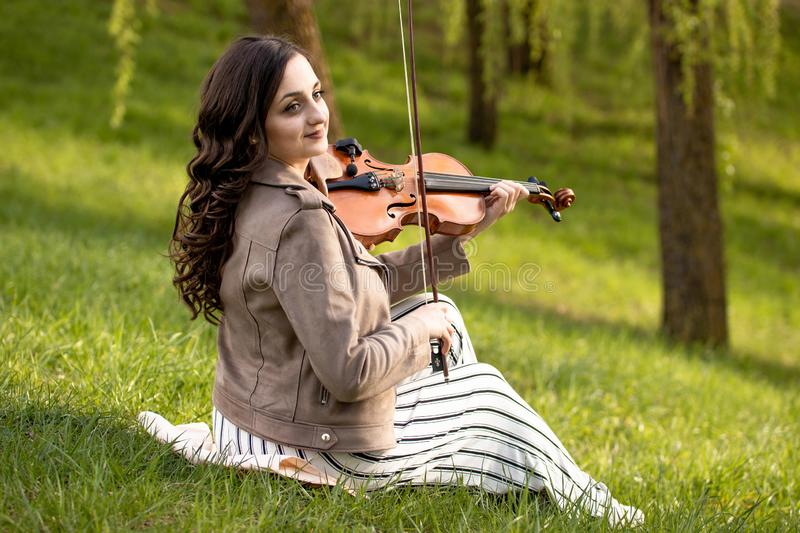 Young woman playing violin in the park royalty free stock photography